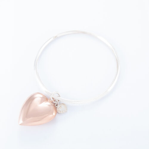 Our 2 Tone Large Puffed Heart Bangle. Shown here, handcrafted in a bevel-edged 925 sterling silver band. Also with a beautiful large puffed rose gold heart. As well as, with a small sterling heart. It's a truly unique and stunning piece. In short, the ultimate gift idea, with twice the love. Or as a self-indulgent purchase to add to your own personal jewelry collection.