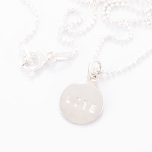 """Our Fine Sterling Silver Small Love Disc Necklace. Shown here, in stunning 925 sterling and stamped """"LOVE"""". In short, this petite piece is sure to give lots of love. The perfect gift for someone special or as a self-indulgent addition to any jewelry collection."""