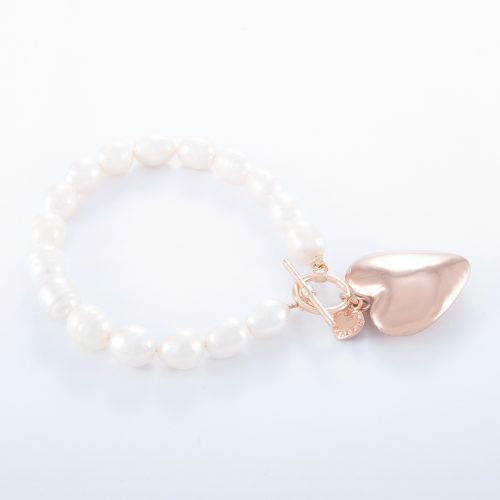 Our Freshwater Pearl Rose Gold Large Puffed Heart Bracelet. Shown here, with a lovely pink gold charm plated over 925 sterling silver. As well as with a rose over sterling small flat heart. In short, this stunning piece is full of love. It's the ideal self-indulgent purchase to add to any personal jewellery collection. Or as the prefect gift for that extra special someone.