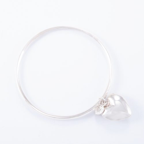 Our Sterling Silver Small Puffed Heart Bangle. Shown here, in hand-made 925 sterling, bevel-edged with a small puffed heart charm. As well as, with a small flat sterling heart.