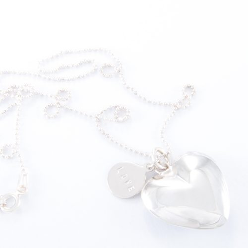Our Fine Sterling Silver Small Puffed Heart Ball Chain Necklace. Shown here beautifully handcrafted in 925 sterling. Also paired with a small sterling love disc. In short, this stunning piece is elegant, timeless, and full of style. The perfect gift idea for someone special. Or as a self-indulgent addition to your own jewelry collection.