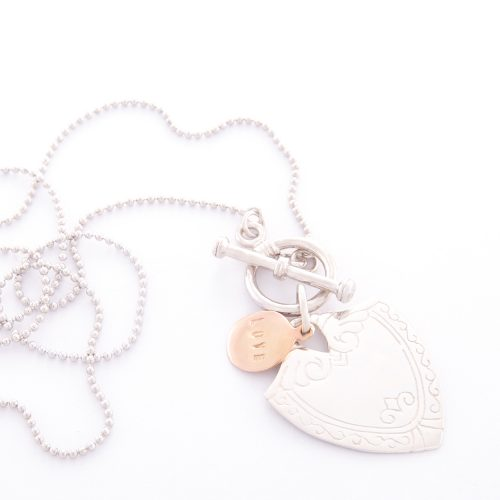 Our Sterling Silver Shield Ball Chain Necklace. Shown here, handcrafted and also engraved in 925 sterling. As well as with a rose gold love disc charm. In short, this piece is simply stunning. The ideal self-indulgent addition to your own personal jewelry collection. Or as the perfect gift for someone extra special.