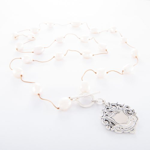 Our Freshwater Pearl Necklace (Spaced 32 Inch) with Large Sterling Silver Shield. Shown here, beautifully handcrafted with a silk cord and 925 sterling fob. In short, this stunning substantial piece is full of charm, elegance, and style. It's the ideal self-indulgent purchase to add to your own jewelry collection. Or as the perfect gift for somebody very special.