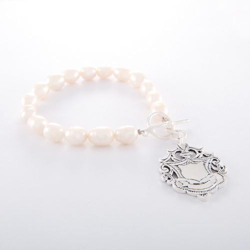 Our Freshwater Pearl Bracelet with Large Sterling Silver Shield. Shown here, with a beautifully handcrafted charm in 925 sterling. In short, this is a stunning timeless piece, made with love. It's the ideal self-indulgent purchase to add to your jewelry collection. Or as the ultimate gift for someone extra special.