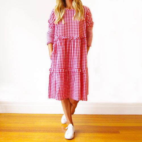 Our Red and White Gingham Dress (Cassi). Is an absolute stunner. Shown here, with unique sheering detail and medium check. As well as comfy side pockets, gorgeous frill detail, and an airy full skirt. What's more, our amazing Cassie comes in 2 sizes and offers a free-size relaxed fit. An S/M for ladies size 10-12 and an M/L for 14 plus. In short, it's the perfect self-indulgent purchase to add to your wardrobe. Or as the gift idea gift for someone extra special.