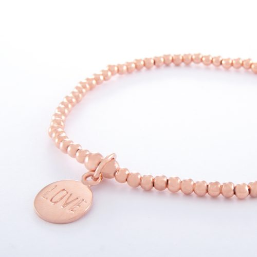 """Our Rose Gold Ball Chain Bracelet and Love Disc. Shown here, beautifully handcrafted in pink gold over 925 sterling. As well as, with a stamped """"Love"""" charm. There's lots of love in this elegant, stunning piece. In short, it's the perfect self-indulgent purchase to add to your own jewelry collection. Or as a unique gift idea for someone extra special."""