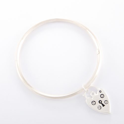 Our Sterling Silver Bangle with Padlock Heart. Shown here, handcrafted beautifully in 925 sterling, with a bevel-edge. As well as a stunning charm. A truly unique and elegant piece. In short, it makes for an amazing gift, with lots of love, for someone very special. Or as the perfect self-indulgent purchase to add to any personal jewelry collection.
